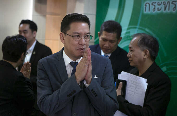 Thai Minister of Digital Economy and Society, Phutthipong Punnakan, center, greets during a news conference to announce the…