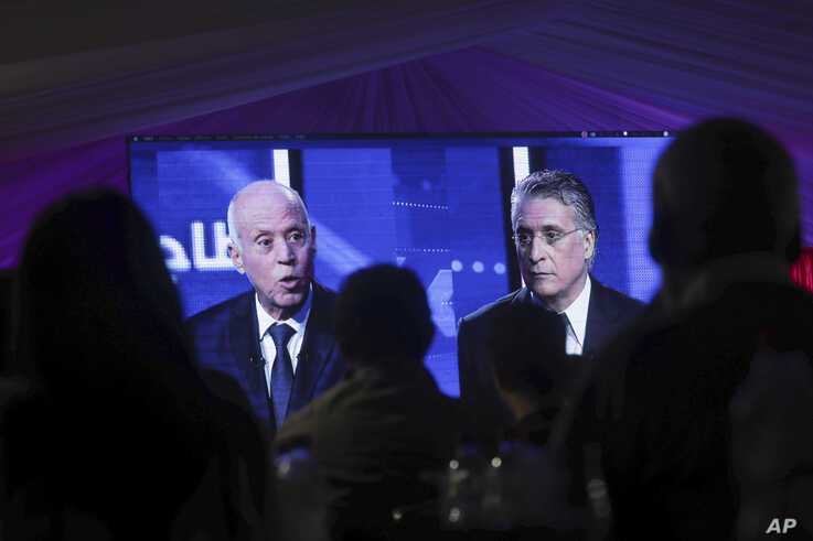 People watch a televised debate between presidential candidates Kais Saied, left, and Nabil Karoui, on the last day of campaigning before the second round of the country's presidential elections, in Tunis, Tunisia, Oct. 11, 2019.