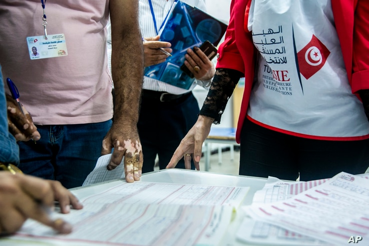 Election officials start counting marked ballots after polling stations closed during a parliamentary election in Tunis, Tunisia, Oct. 6, 2019.