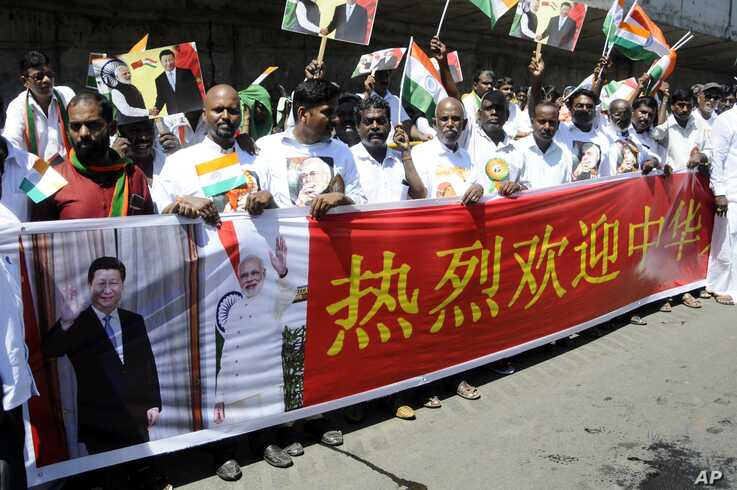 Indians hold a banner welcoming Chinese President Xi Jinping outside the airport in Chennai, India, Oct. 11, 2019.