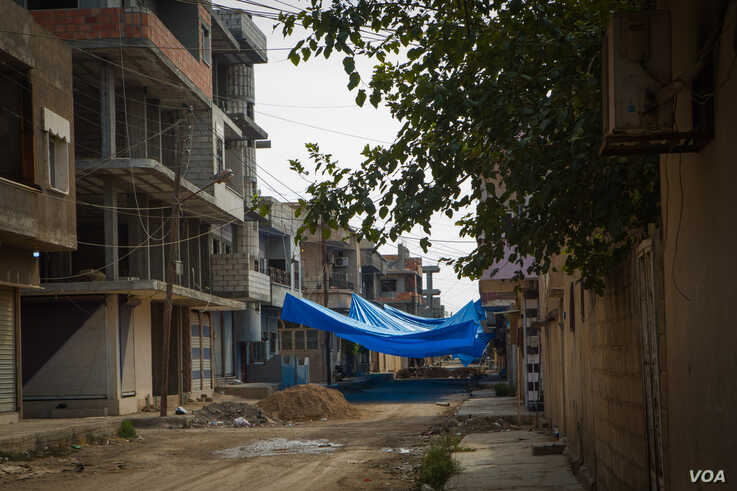 Many neighborhoods have covered their streets with tarps so they go unseen by the drones that have been flying over the city at night, in Darbasiyah, Syria, Oct. 22, 2019. (VOA/Yan Boechat)