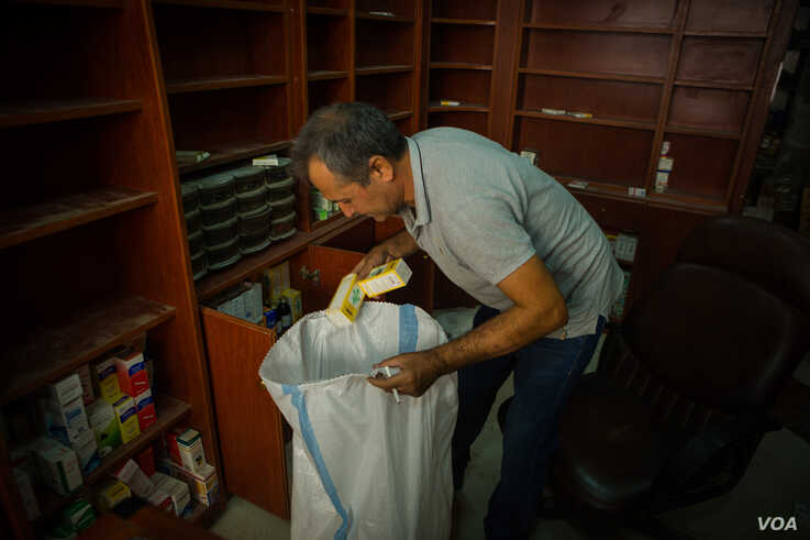 Adnan Mala Ali, a pharmacist with three small children, packs his medicines from his his shop before evacuating from Darbasiyah, Syria, Oct. 22, 2019. (VOA/Yan Boechat)
