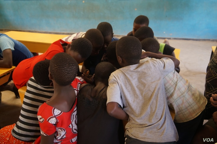 A shortage of textbooks in Malawi primary schools forces teachers to divide students into groups that share one book. (L. Masina/VOA)