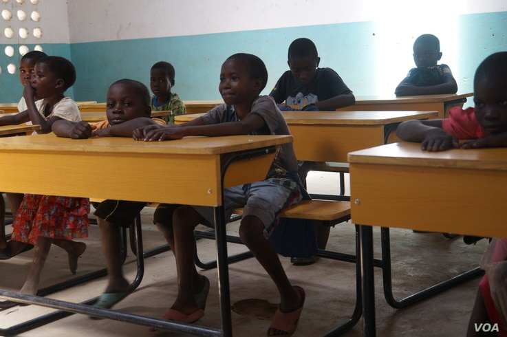 These children at Mazembe Primary School used to sit on the floor before Ripple Africa donated desks for them. (L. Masina/VOA)