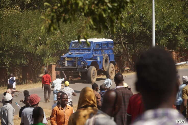 Protesters throw stones at a police armoured vehicle during a post-elections demonstration in Malawi's the capital Lilongwe. (Lameck Masina/VOA)