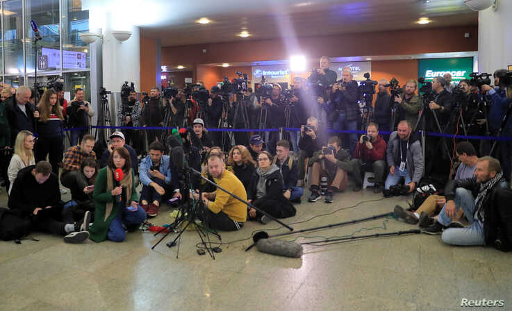 Journalists wait for Maria Butina's arrival, at Sheremetyevo International Airport outside Moscow, Russia, Oct. 26, 2019.