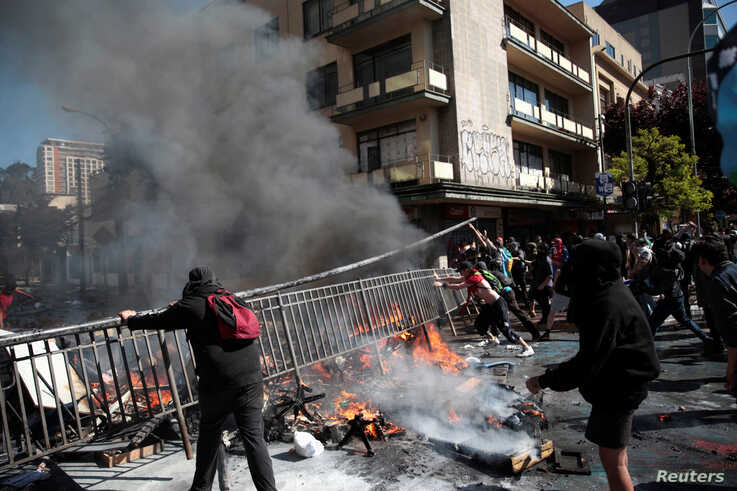 Demonstrators move a fence to use as a barricade during a protest in Concepcion, Chile, Oct. 23, 2019.