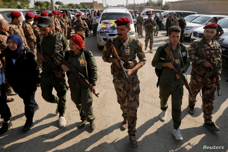 FILE - Fighters of Syrian Democratic Forces (SDF) take part in a funeral procession for comrades killed during clashes in the northeastern Syrian town of Ras al-Ayn, in the town of Qamishli, Syria, Oct, 22, 2019.