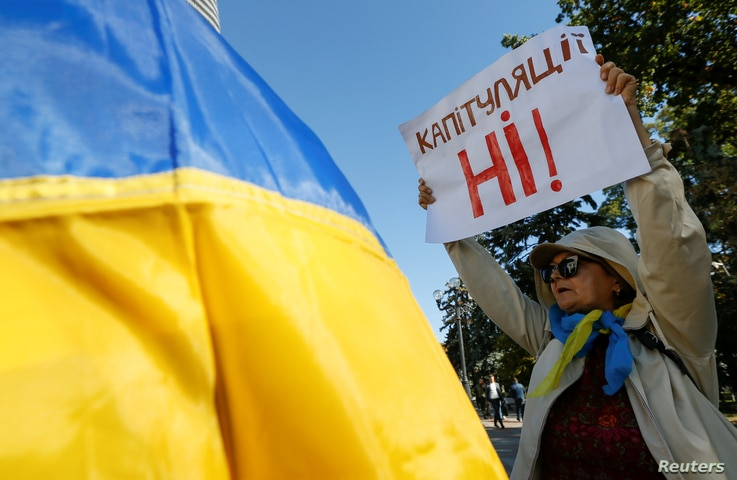 "A woman attends a rally against the approval of a local election accord, in Kyiv, Ukraine, Oct. 2, 2019. Her sign reads: ""No capitulation!"""