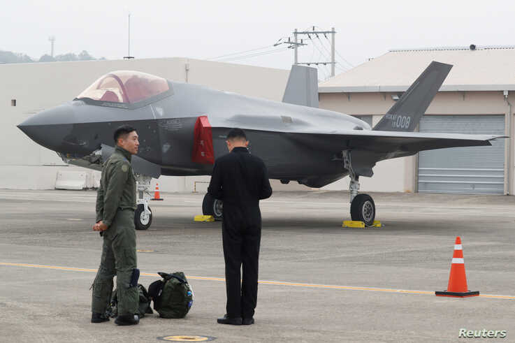 A South Korean fighter pilot, left, stands next to his F-35 stealth fighter during a ceremony to mark the 71st Armed Forces Day