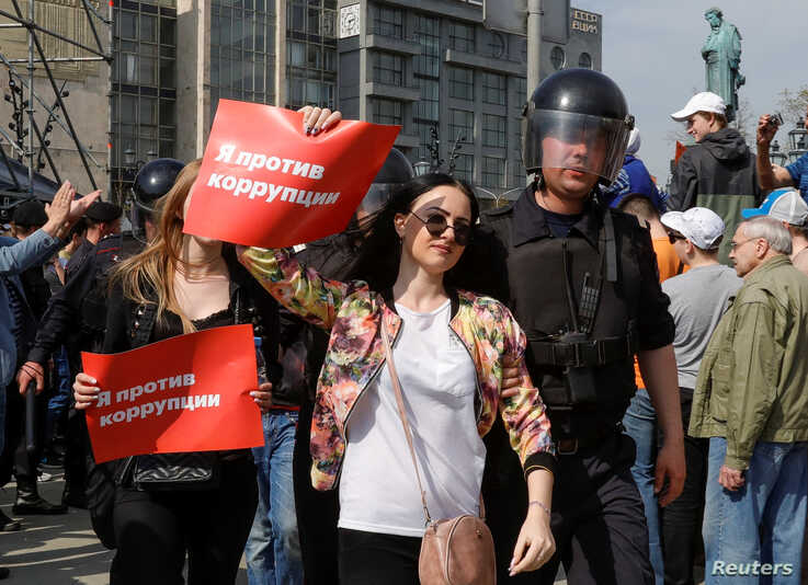 """FILE - Police officers detain opposition supporters during a protest in Moscow, Russia, May 5, 2018. The posters reads """"I am against corruption."""""""