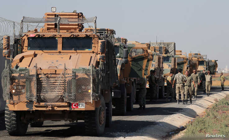 Turkish soldiers stand near military trucks in the village of Yabisa, near the Turkish-Syrian border, Syria, Oct. 12, 2019.