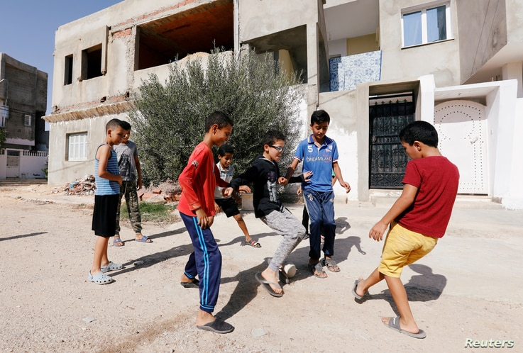Boys play near the house of Fakher Hmidi in Thina district of Sfax, Tunisia, Oct. 15, 2019.