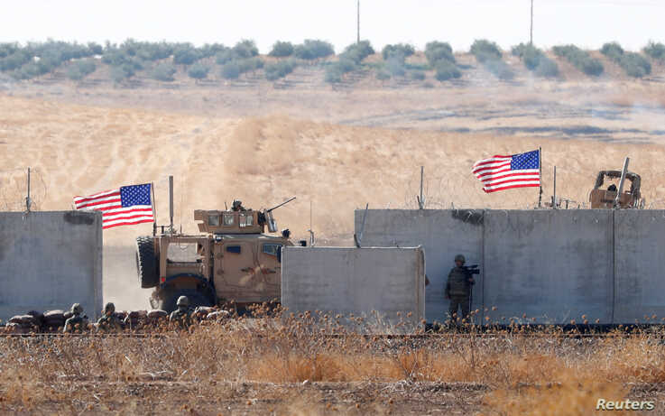 U.S. troops are seen behind the Turkish border walls in northern Syria, Sept. 8, 2019.