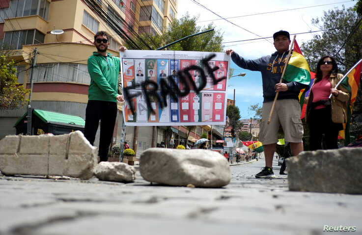 """Demonstrators hold a sign reading """"Fraud"""" in La Paz, Bolivia, Oct. 29, 2019."""