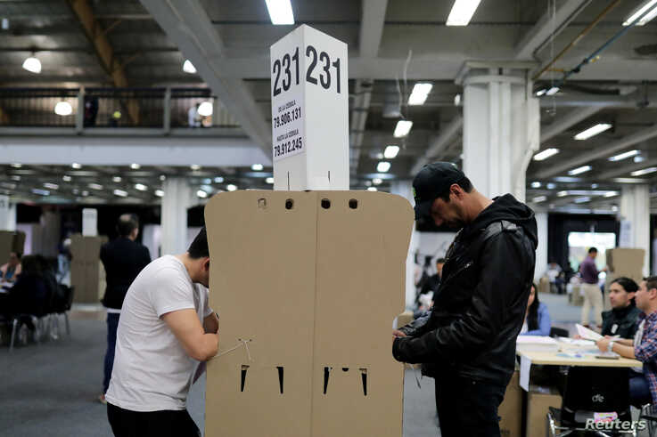 People cast their votes at a polling station during the elections for mayors and governors, in Bogota, Colombia, Oct. 27, 2019.