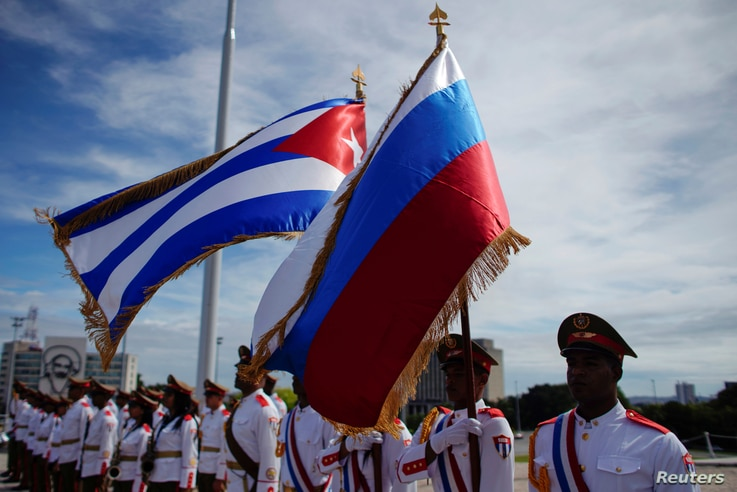 Honor guards hold a Russian and a Cuban flag during a wreath-laying ceremony with Russia's Prime Minister Dmitry Medvedev (not pictured) at the Jose Marti monument in Havana, Cuba, Oct. 3, 2019.
