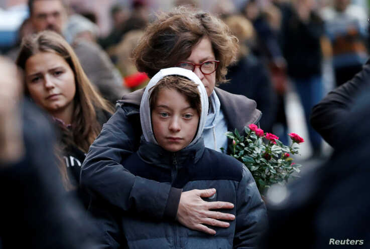 People mourn outside the synagogue in Halle, Germany, a day after two people were killed in a shooting.