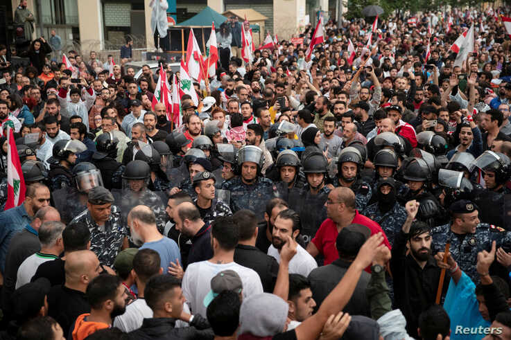 Riot police stand guard between two groups of demonstrators during ongoing anti-government protests in downtown Beirut, Lebanon, Oct. 24, 2019.