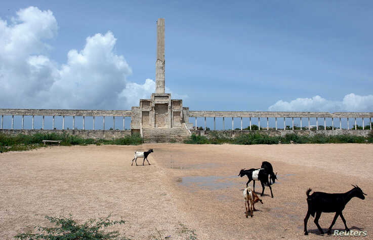 FILE - Goats graze near the Dhagaxtuur statue, the area of former government offices in Somalia's capital Mogadishu, July 30, 2006.