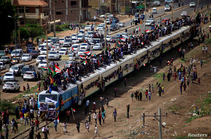Sudanese civilians ride on the train to join the celebrations of the signing of the power sharing deal, that paves the way for a transitional government, in Khartoum, Aug. 17, 2019.