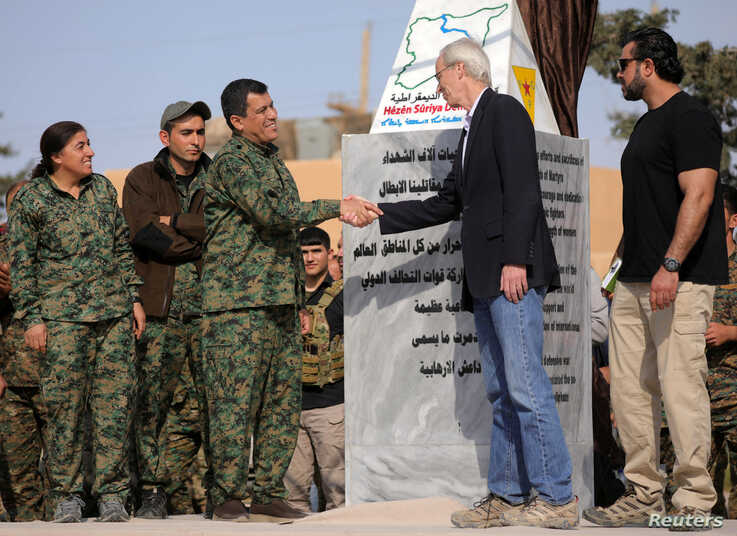 FILE - Mazloum Kobani, SDF's commander in chief, shakes hands with the advisor for the U.S. Department of State in northern Syria William Robak, at al-Omar oil field in Deir Al Zor, Syria, March 23, 2019.