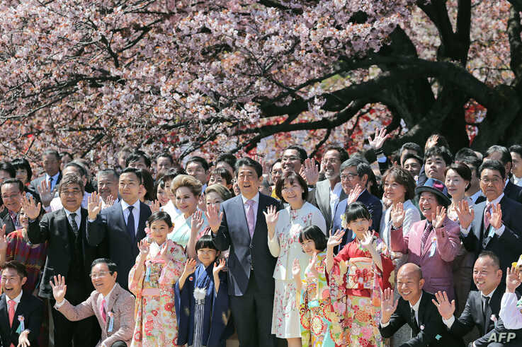 Japanese Prime Minister Shinzo Abe (centre L) and his wife Akie (center R) pose for pictures with their guests during his…