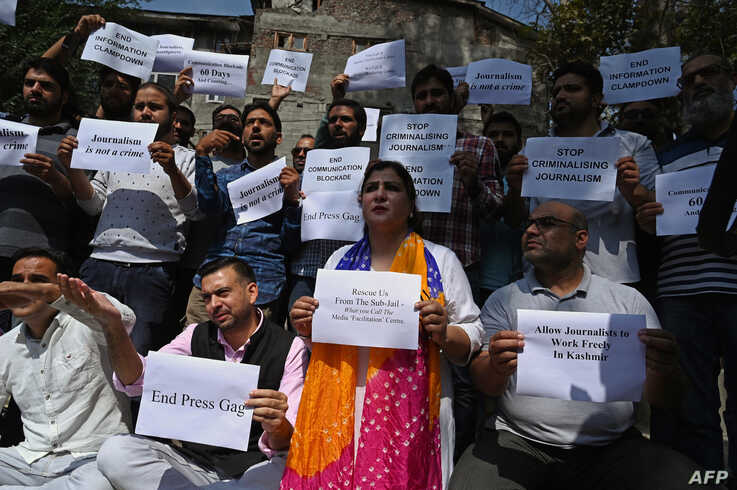 Journalists hold signs during a protest against the ongoing restrictions of the Internet and mobile phone networks at the…