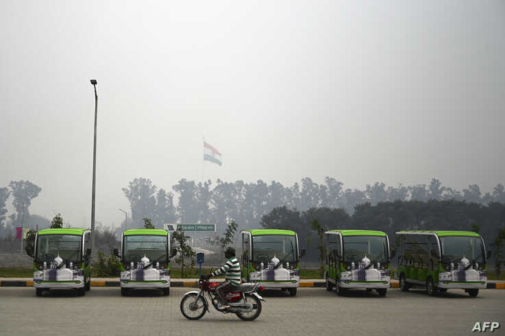 A Pakistani motorcyclist rides past golf carts, which are for Sikh pilgrims, at the immigration center ahead of the opening…