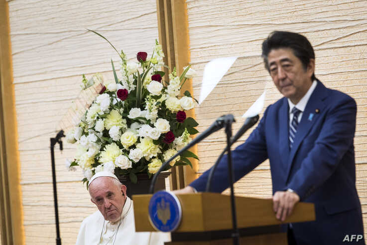 Japan's Prime Minister Shinzo Abe, right, delivers a speech as Pope Francis listens in Tokyo, Nov. 25, 2019.