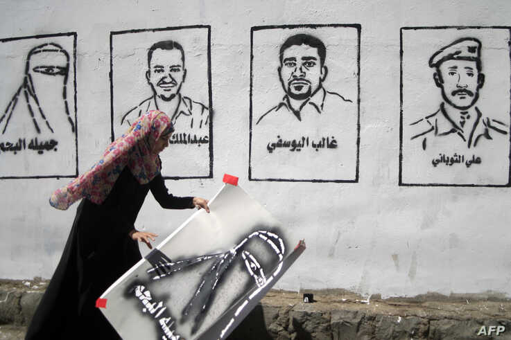 """A Yemeni graffiti artist paints faces of victims of an al-Qaida militant attack on a wall during an """"anti-terrorism"""" campaign…"""