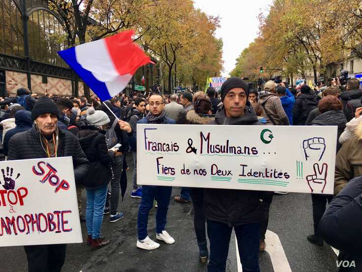 A man (M) carries banner reading, French and Muslims, proud of our identity, Paris, Nov. 10, 2019. (Lisa Bryant/VOA)