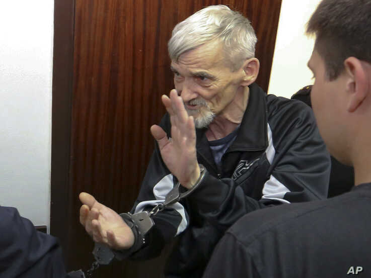 Russian historian Yury Dmitriyev is escorted into a court room in the city of Petrozavodsk, northwestern Russia in Petrozavodsk, Russia, Thursday, June 28, 2018.