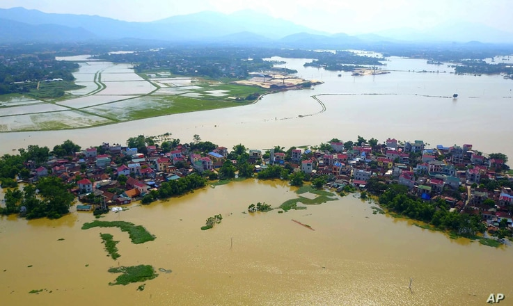 In this photo taken on July 22, 2018, a village is submerged in flood water in the suburb of Hanoi, Vietnam. Flooding triggered…