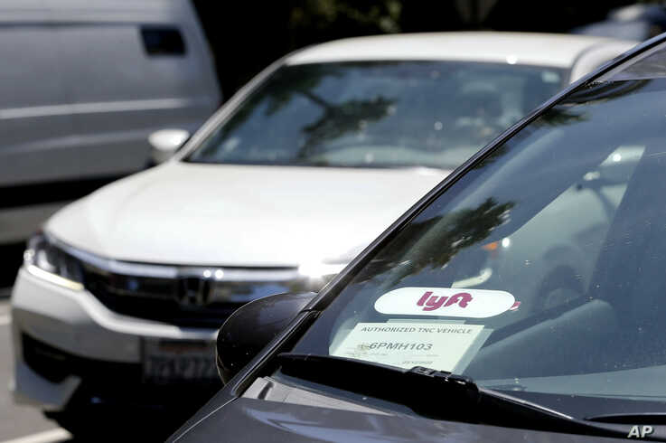 FILE - In this July 9, 2019, file photo a Lyft ride-share car waits at a stoplight in Sacramento, Calif. California lawmakers…