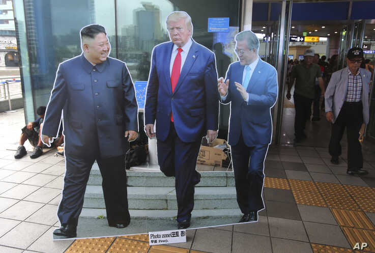 Cut-out photos of North Korean leader Kim Jong Un, left, U.S. President Donald Trump, and South Korean President Moon Jae-in,…