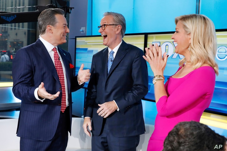 """Fox News Chief National Correspondent Ed Henry, left, is welcomed by co-hosts Steve Doocy and Ainsley Earhardt on the """"Fox &…"""