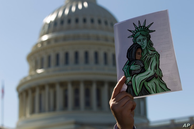 Faith leaders and members of human rights groups protest outside of the U.S. Capitol during a demonstration calling congress...