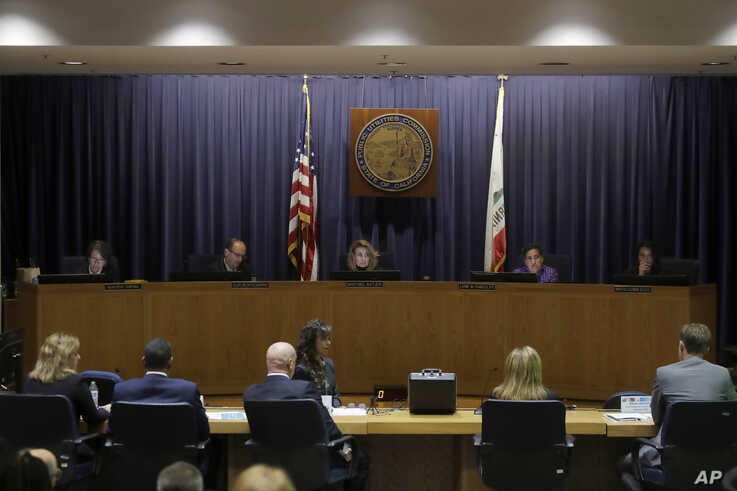 California Public Utilities Commission President Marybel Batjer, center rear, and commissioners listen as representatives of…