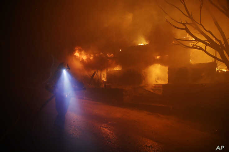 A firefighters gets in position to hose down flames as a home burns in the Getty fire area along Tigertail Road, Oct. 28, 2019, in Los Angeles.