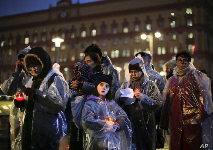 People hold candles as they gather at a monument outside the former KGB headquarters in Moscow, Russia, Oct. 29, 2019, in an annual commemoration of the victims of purges under Soviet dictator Joseph Stalin.