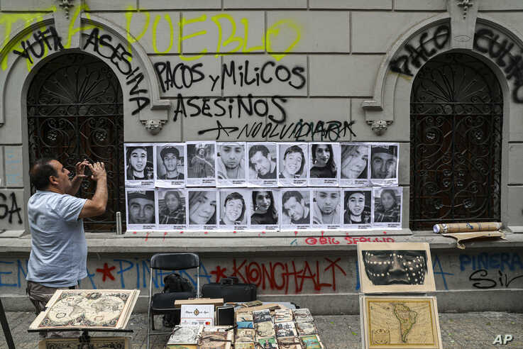 A man takes a photo of portraits of people that have died during anti-government protests in Santiago, Chile, Friday, Nov. 1,…