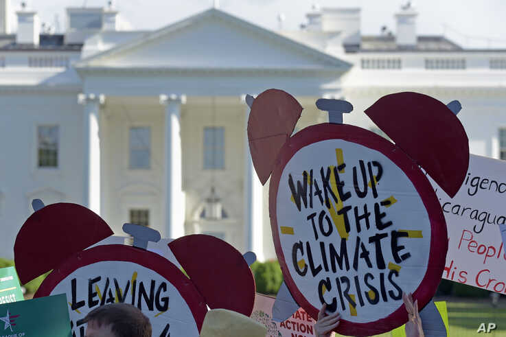 FILE- Protesters gather outside the White House in Washington to protest President Donald Trump's decision to withdraw the Unites States from the Paris climate change accord, June 1, 2017.