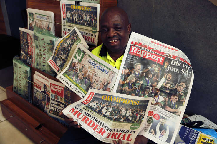 A newspaper seller poses for a photograph on Nov. 3, 2019 in Johannesburg with the banner headlines of South Africa's Rugby World Cup win over England on Saturday. South Africa beat England 32-12.