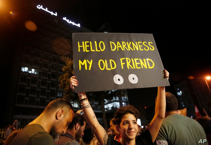 An anti-government protester holds up a placard in front the Lebanese electricity company headquarters, during ongoing protests…