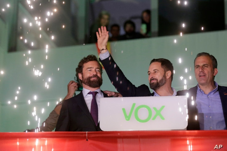 Santiago Abascal, leader of far-right Vox Party, waves to supporters as fireworks go off outside the party headquarters after the announcement of the general election first results, in Madrid, Spain, Nov. 10, 2019.