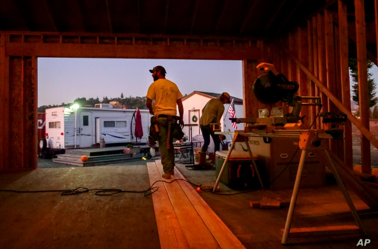 In this Monday, Nov. 4, 2019, photo, Bobbie Chandler, left, and his wife, Jenna, stand in the home they are building in Santa…