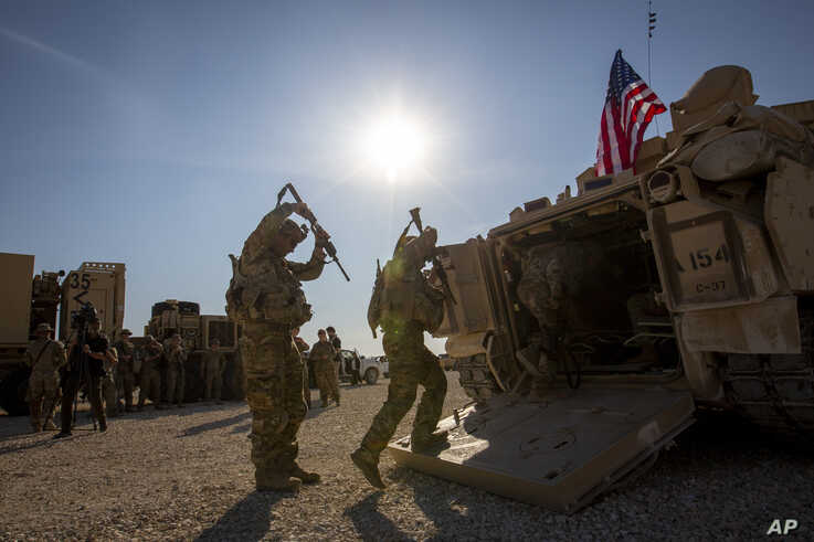 Crewmen enter Bradley fighting vehicles at a US military base at an undisclosed location in Northeastern Syria, Monday, Nov. 11…
