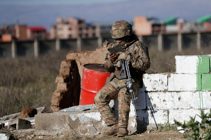 A soldier guarding the Senkata fuel plant reads from a mobile device, in El Alto, Bolivia, Friday, Nov. 22, 2019. At least…