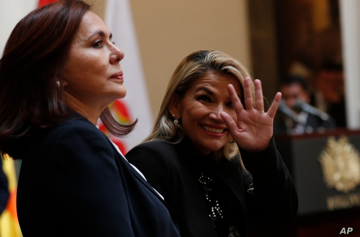 Accompanied by Bolivia's Foreign Minister Karen Longaric, interim President Jeanine Anez waves to journalists during a protocol…